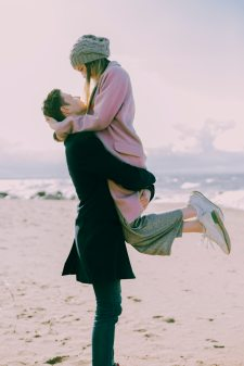 man-in-gray-coat-carrying-woman-wearing-pink-coat-in-beach-698885